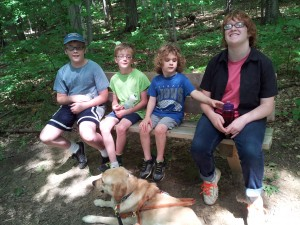 A'Kos with Liam, Jarod, Kender, and Caitlin, taking a bench break while out on a hike